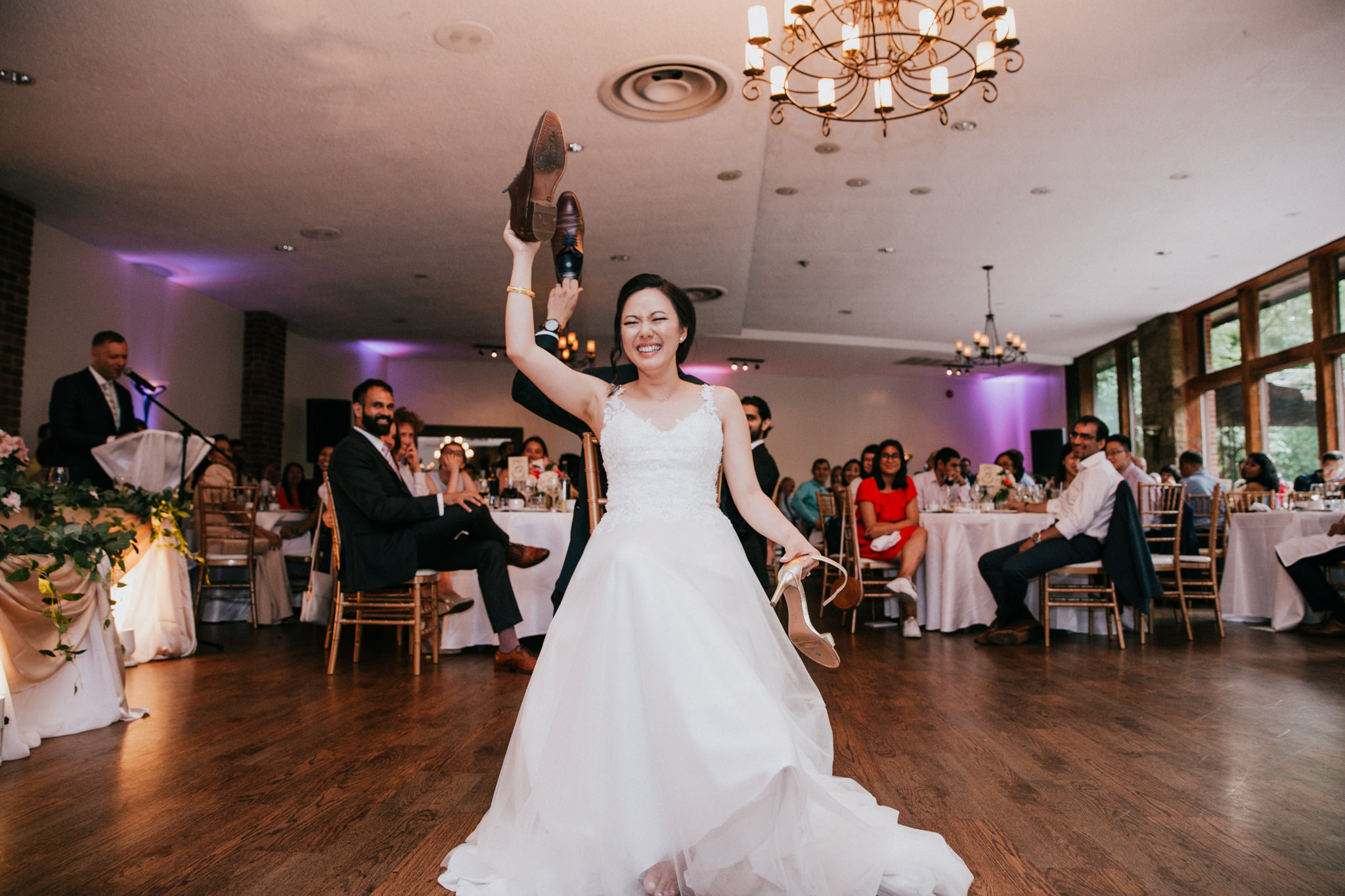 bride holding a shoe up during a wedding game